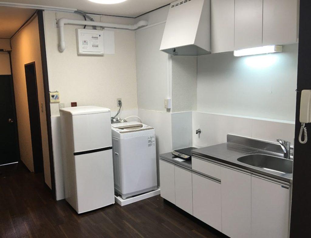 白が基調カラーのキッチンと冷蔵庫、そして洗濯機